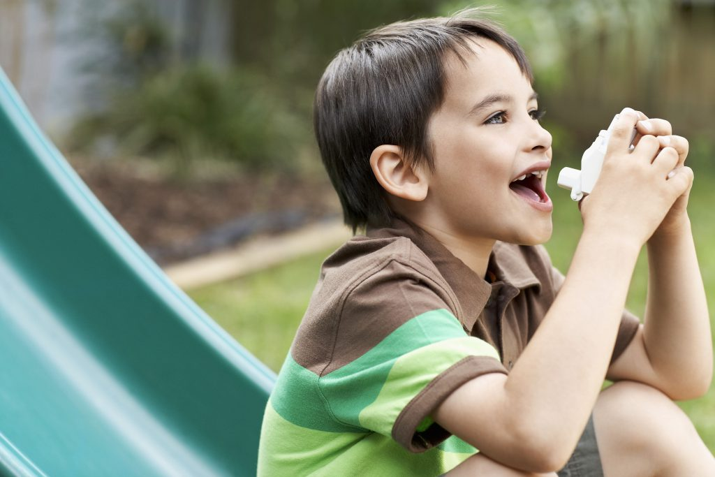 Boy using asthma inhaler in the garden